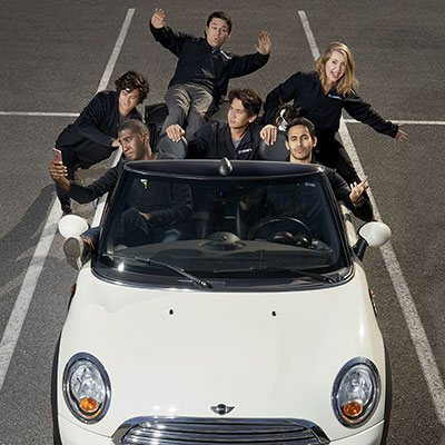 Students posing in a convertible car