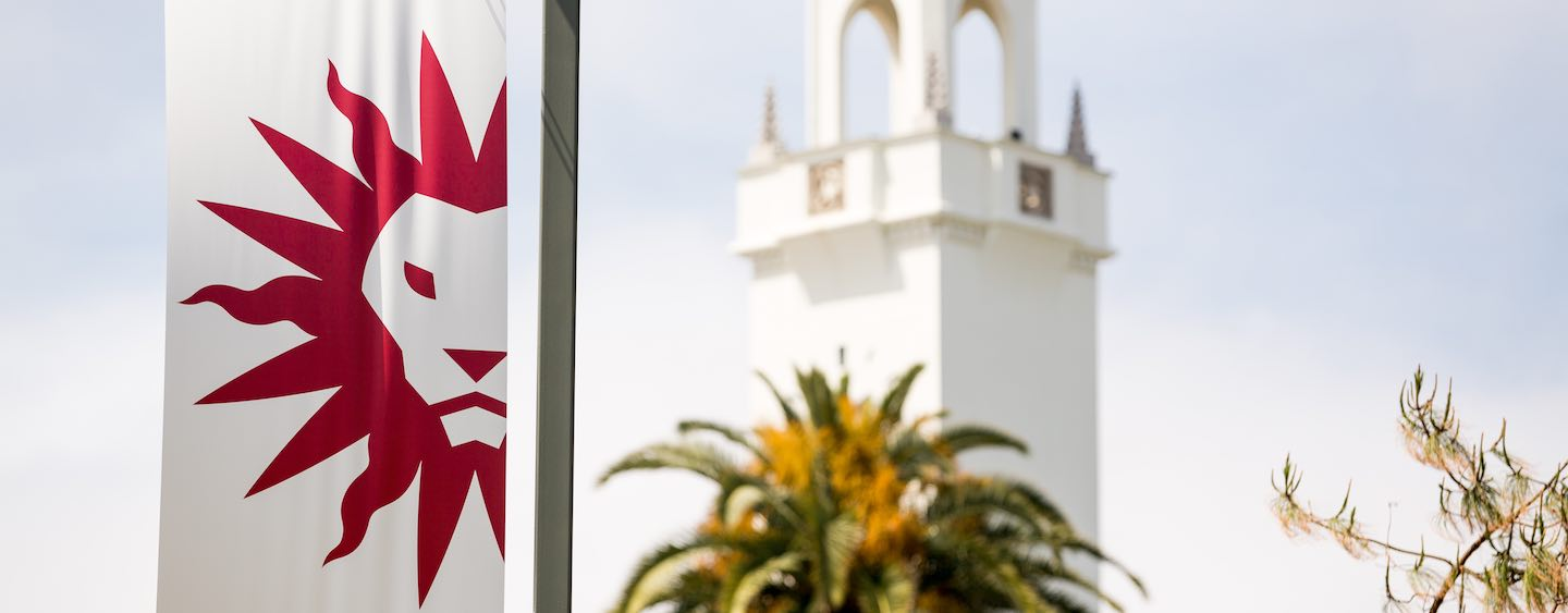 Street pole banner displaying LMU spirit mark with chapel tower and palm tree in background